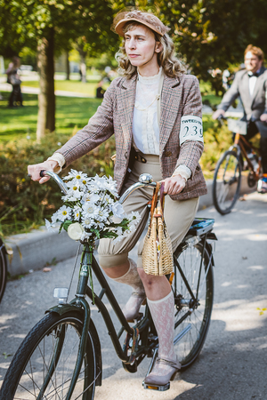 ladys: Toronto, Canada - September 20, 2014: Unidentified participants of Tweed Ride Toronto riding on their bicycles. This annual event also known as Tweed Run is dedicated to the style of old England: people dress up in vintage style clothes and try to reconst Editorial