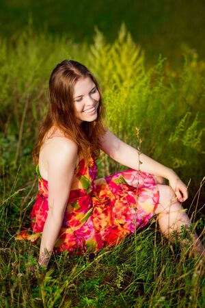 ginger hair: Redhaired young woman with long ginger hair and closed eyes sitting on grass and smiling on hot sunny day. Carefree freedom and leisure concept