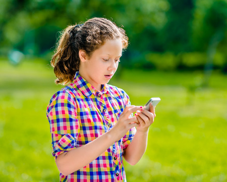 Surprised teenage girl in casual clothes with smartphone in her hand looking at screen reading a message    texting and chatting
