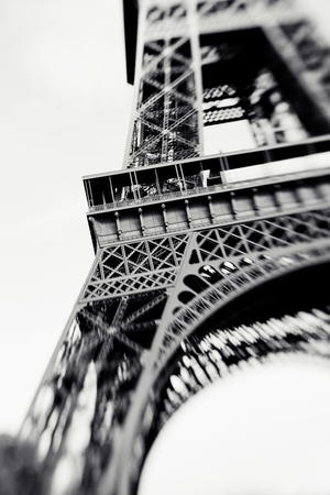 Blurred shot of the Eiffel Tower in Paris France selective focus on details. Lensbaby photo of Eiffel Tower vintage black and white colors