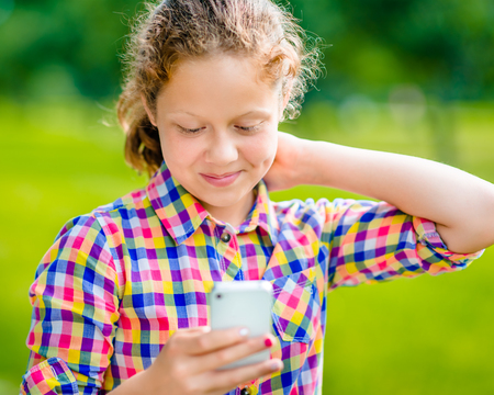 Beautiful smiling teenage girl in casual clothes with smartphone in her hand looking at screen reading a message  in sunny day in summer park