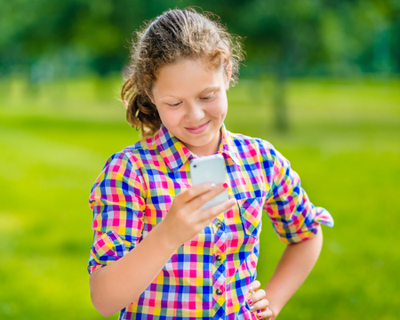Sweet smiling teenage girl in casual clothes with smartphone in her hand looking at screen reading a message in sunny day in summer park