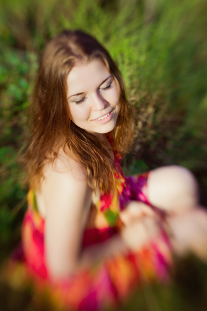 Beautiful smiling ginger girl with closed eyes sitting on grass in summer park on sunny day. Selective focus on one eye lensbaby blur effect. Relax and rest concept