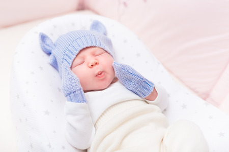 Cute little baby wearing knitted blue hat with ears and mittens lying in beautiful cradle with closed eyes and making funny face. Security and childcare concept