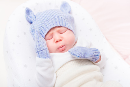 Sweet little baby wearing knitted blue hat with ears and mittens lying in beautiful cradle with closed eyes and making sad face. Security and childcare concept