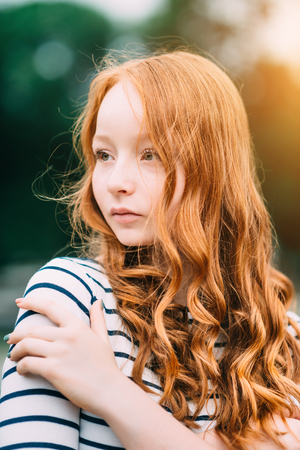 A beautiful teenage girl with long curly ginger hair and green eyes hugging herself in summer park. Outdoor portrait of attractive red-haired young woman in evening at sunset