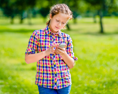 Beautiful smiling teenage girl in casual clothes with smartphone in her hand, looking at screen, reading a message, using Facebook, texting and chatting