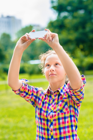 Adorable teenage girl taking picture with smartphone in sunny day in summer park. Teenage girl taking selfie with smartphone Фото со стока