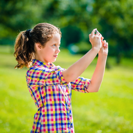 Beautiful teenage girl taking picture with smartphone in sunny day in summer park. Teenage girl taking selfie with smartphone