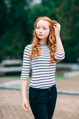 Outdoor portrait of beautiful girl with long curly red hair and green eyes. Young redhead woman touching her ginger hair. Teenage red-haired girl standing  in summer park. Femininity concept Фото со стока