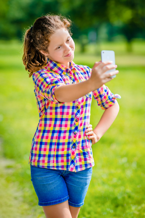 Lovely smiling girl posing and taking selfie with smartphone in sunny day in summer park. Teenage girl taking picture with smartphone