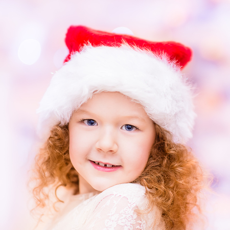 Closeup portrait of a beautiful red-haired little girl with long curly hair wearing Santa Claus Christmas hat. Christmas and New Year celebration concept