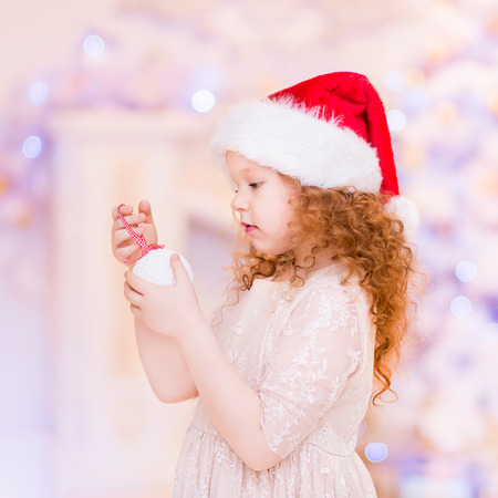 redhaired: Cute red-haired little girl with long curly hair wearing Santa Claus hat holding white Christmas ball and looking at it. Christmas and New Year celebration concept Stock Photo