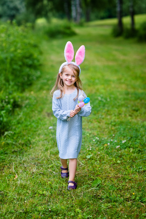 Adorable little girl with long blond hair wearing rabbit or bunny ears and blue knitted dress. Smiling little girl holding bunch of painted colour eggs and walking in spring park. Easter celebrations Фото со стока