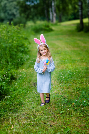 Smiling little girl with long blond hair wearing rabbit or bunny ears and blue knitted dress. Cute little girl holding bunch of painted colour eggs and walking in spring park. Easter celebrations Фото со стока