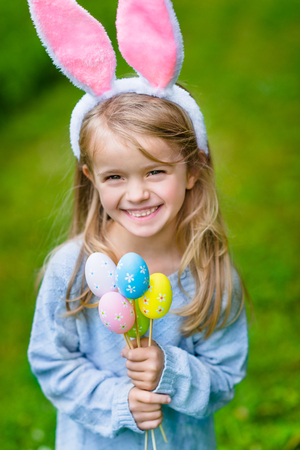 Beautiful smiling little girl with long blond hair wearing pink rabbit or bunny ears and blue knitted dress and holding bunch of painted colour eggs on sunny day in spring park. Easter celebrations Фото со стока