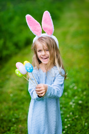 Cute laughing blond little girl wearing white and punk rabbit or bunny ears and blue knitted dress and holding bunch of painted colour eggs on sunny day in spring park. Easter celebrations