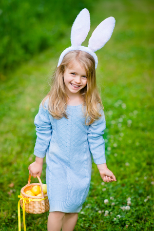 Smiling little girl with long blond hair wearing white rabbit bunny ears and blue knitted dress and holding wicker basket with yellow eggs and ribbon on sunny day in spring park. Easter celebrations Фото со стока