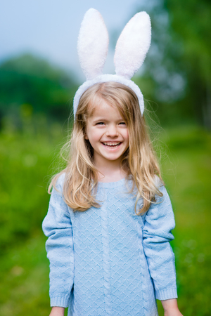 Outdoor portrait of beautiful smiling little girl with long blond hair wearing white rabbit or bunny ears and blue knitted dress on sunny day in spring park. Easter celebrations Фото со стока