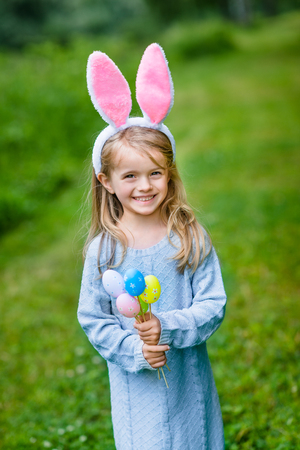Portrait of smiling little girl with long blond hair wearing rabbit or bunny ears and blue knitted dress and holding bunch of painted colour eggs on sunny day in spring park. Easter celebrations