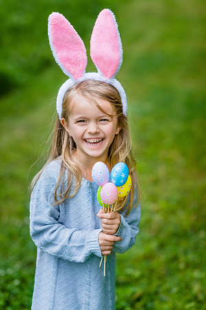 Adorable laughing little girl with long blond hair wearing pink rabbit or bunny ears and blue knitted dress and holding bunch of painted colour eggs on sunny day in spring park. Easter celebrations