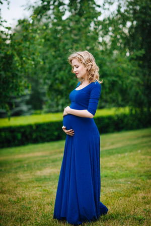 Pretty young pregnant woman in blue dress with long blond curly hair holding her belly and looking at it in summer park on rainy day. Pregnancy and femininity concept. Waterdrops on blue dress Фото со стока