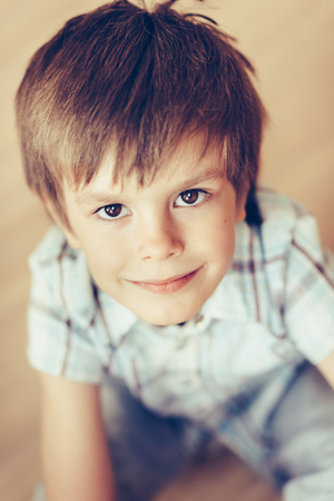 Closeup portrait of handsome smiling little boy with brown eyes wearing checkered shirt sitting on floor looking at camera. Happy childhood concept, selective focus on eyes, top view, instagram filter Фото со стока