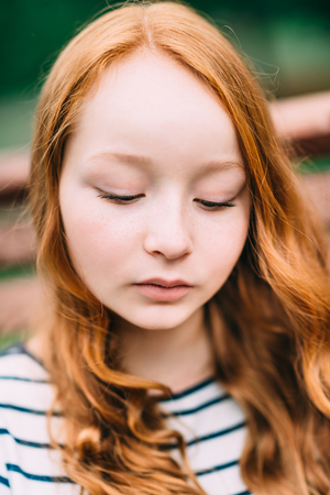 Close-up portrait of lovely thoughtful girl with long curly red hair in summer park. Outdoor portrait of a red-haired teenage girl. Adorable young redhead longhaired woman Фото со стока