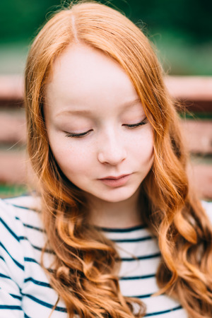 Close-up portrait of beautiful modest girl with long curly red hair in summer park. Outdoor portrait of a red-haired teenage girl. Adorable young redhead longhaired woman