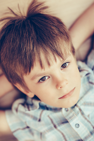 Closeup portrait of pensive little boy with brown eyes wearing checkered shirt lying on floor and looking at camera. Happy childhood concept, selective focus on eyes, top view, instagram filters Фото со стока