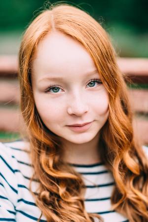 夏の公園で長い巻き毛の赤い髪のはかなり笑みを浮かべて少女のクローズ アップの肖像画。赤髪の 10 代の少女の屋外のポートレート。愛らしい若い
