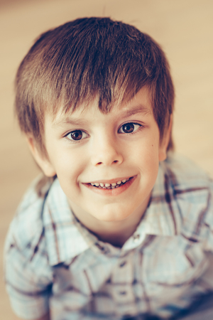 Closeup portrait of cute smiling little boy with brown eyes wearing checkered shirt sitting on floor and looking at camera. Happy childhood concept, selective focus on eyes, top view Фото со стока