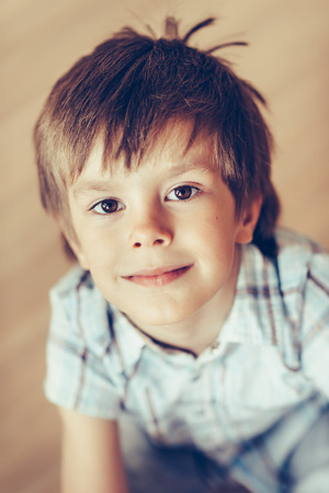 Closeup portrait of adorable smiling little boy with brown eyes wearing checkered shirt sitting on floor looking at camera. Happy childhood concept, selective focus on eyes, top view