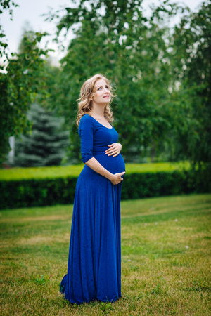 Pretty young pregnant woman in blue dress with long blond curly hair holding her belly, smiling and looking at sky in summer park on rainy day. Pregnancy and femininity concept. Waterdrops on dress