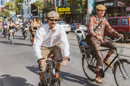 Toronto, Canada - September 20, 2014: Unidentified participants of Tweed Ride Toronto in vintage style clothes riding on their bicycles. This event is dedicated to the style of old England Stock Photo - 54682585