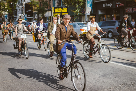 kepi: Toronto, Canada - September 20, 2014: Unidentified participants of Tweed Ride Toronto in vintage style clothes riding on their bicycles. This event is dedicated to the style of old England
