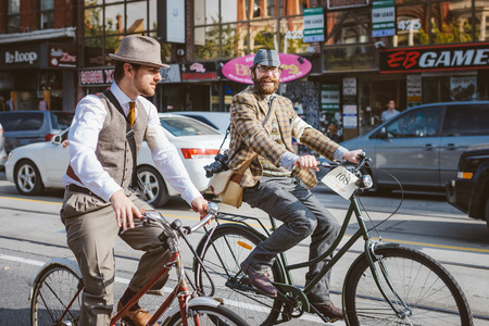 tweed: Toronto, Canada - September 20, 2014: Unidentified participants of Tweed Ride Toronto in vintage style clothes riding on their bicycles. This event is dedicated to the style of old England