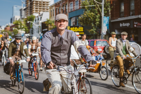 parades: Toronto, Canada - September 20, 2014: Unidentified participants of Tweed Ride Toronto in vintage style clothes riding on their bicycles. This event is dedicated to the style of old England