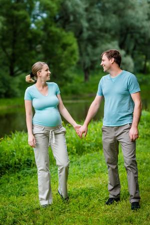 愛らしい若い妊婦と幸せなハンサム男笑顔、お互い手をつないで、夏の公園でお互いを見ています。幸せな家族と妊娠の概念。母の日