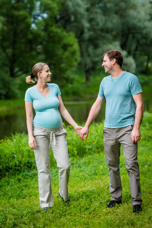 Adorable young pregnant woman and happy handsome man smiling, holding each other hands and looking at each other in summer park. Happy family and pregnancy concept. Mother's Day Banque d'images