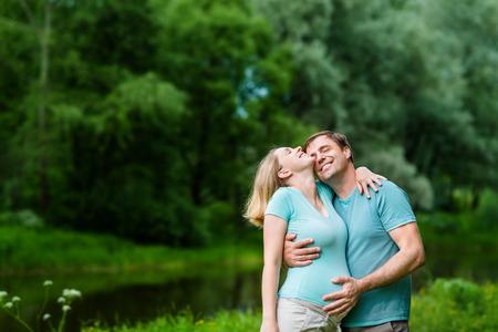 笑みを浮かべてのハンサムな男夏の公園で彼女の腹に触れると彼女の美しい若い妊婦を抱き締めます。幸せな家族と妊娠の概念。母の日