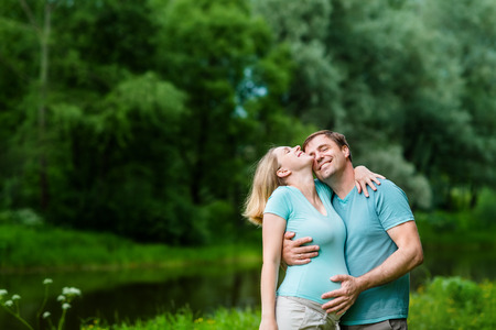 Smiling handsome man hugging her beautiful young pregnant woman and touching her belly in summer park. Happy family and pregnancy concept. Mother's Day