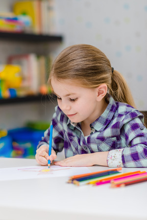 Cute smiling little girl with blond hair sitting at white table and drawing with multicolored pencils