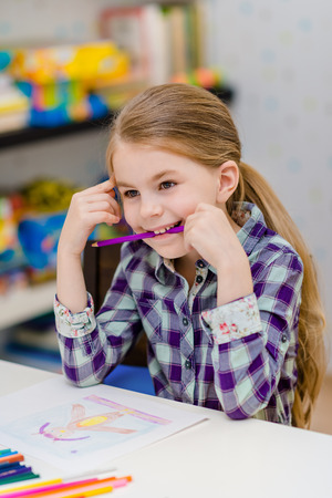 Funny little girl with blond hair sitting at white table and holding purple pencil in her mouth Фото со стока