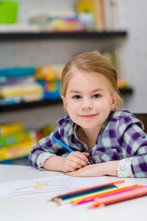 Lovely smiling little girl with blond hair sitting at white table with multicolored pencils and looking at camera