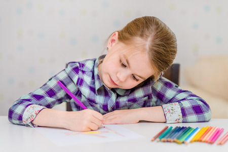 Beautiful pensive little girl with blond hair sitting at white table and drawing with multicolored pencils Banque d'images