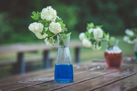 白いアジサイと雨の日の濡れた木製テーブルで色水でガラスの花瓶。雨の公園や庭での庭のベンチの緑の葉と白い花の房を持つ船