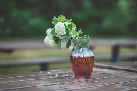 雨の日に濡れた木製テーブルの上の赤い水でガラスの花瓶に白いアジサイの花束。雨の公園や庭で庭のベンチに葉の緑と白い花の束