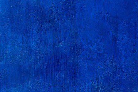 Old scratched and chapped painted royal blue wall. Abstract textured colored background, empty template