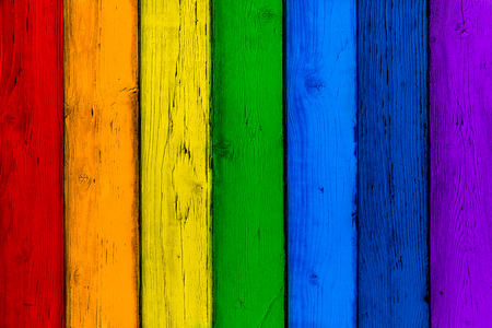 Natural wooden rainbow colored boards. Painted wooden multicolored vertical planks. Abstract textured many-colored background, empty template. Red, orange, yellow, green, blue, violet planks of wood